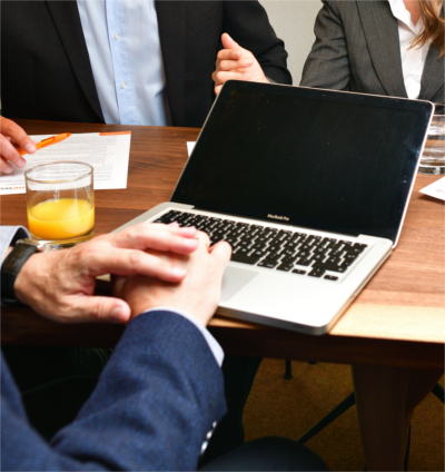 Mehrere Menschen an einem Tisch, die arbeiten. Ein Laptop steht in der Mitte.