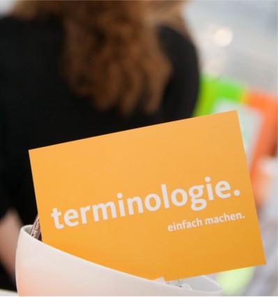 """Eine orange Postkarte mit dem Spruch """"Terminologie. Einfach machen."""""""