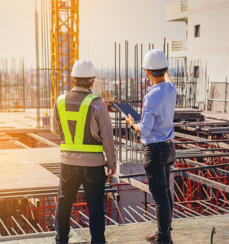 Zwei Bauarbeiter auf einer Baustelle, sie diskutieren den Baufortschritt.