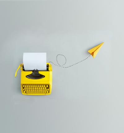 Transkreation; gelbe Schreibmaschine mit gelbem Papierflieger